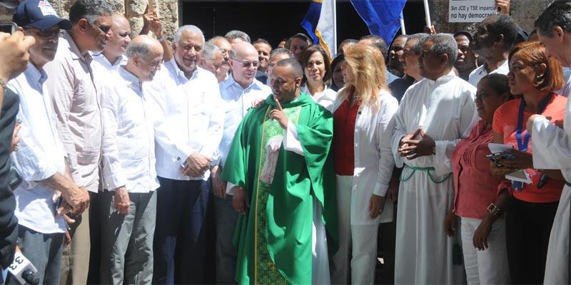 Dirigentes de oposición junto a un sacerdote católico