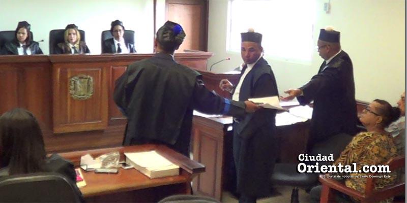 El abogado José Sánchez toma de manos del Ministerio Púbico las fotos de La Tablita que él se opuso a que fueran presentadas como pruebas
