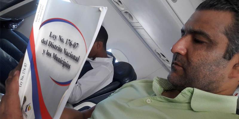 Luis Alberto Tejeda lee la Ley 176-07 dentro de un avión.