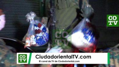 Photo of Con el fusil en el pecho y, en cada mano, una bolsa de comida en  medio del toque de queda