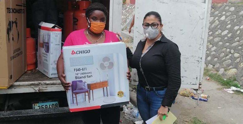 Una feliz ganadora recibe su regalo de manos de una colaboradora de Danilo Mesa