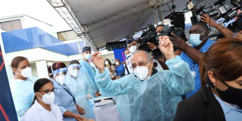 El Ministro de Salud, como si fuera un actor, se exhibe ante las cámaras con una jeringa en una mano y una ampolla con la vacuna en otra.