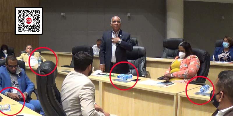En los circulos rojos, las botellas plásticas con agua servida a los regidores