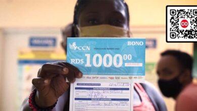 Una mujer muestra su tarjeta d evacunación junto al bono por mil pesos que le obsequió El Boli